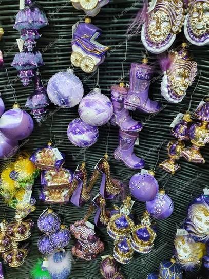 Fialové vianočné ozdoby na stromček v tvare topánok, kráľovských korún, topánok na podpätku a karnevalových masiek.