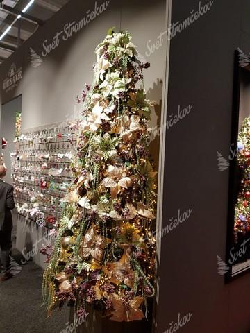 Vianočný stromček ozdobený zlatými ozdobami a zlatými kvetmi .