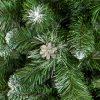 Detail vetvičiek umelého vianočného stromčeka borovica Strieborná . Zelené PVC vetvičky na koncoch zafarbené do biela. v strede obrázku pekná strieborná šiška .