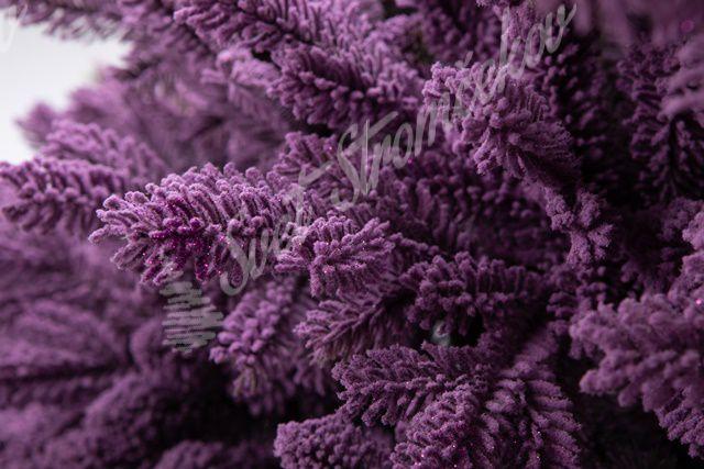 Detailní fotografie purpurových větviček umělého vánočního stromku.