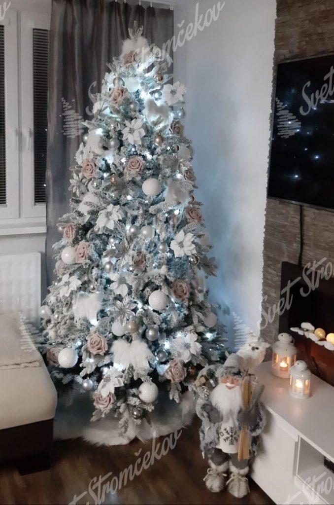 Biely vianočný stromček ozdobený bielými kvetmi a guľami .