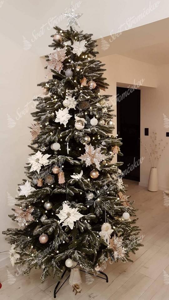 Zasnežený vianočný stromček 3D ozdobený bielými kvetmi a zlatými guľami .