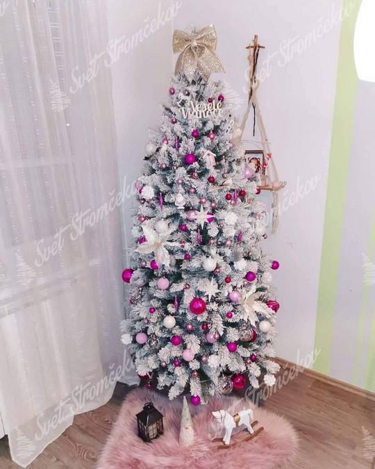 Biely vianočný stromček ozdobený ružovými a bielými guľami spolu s bielými hviezdičkami.