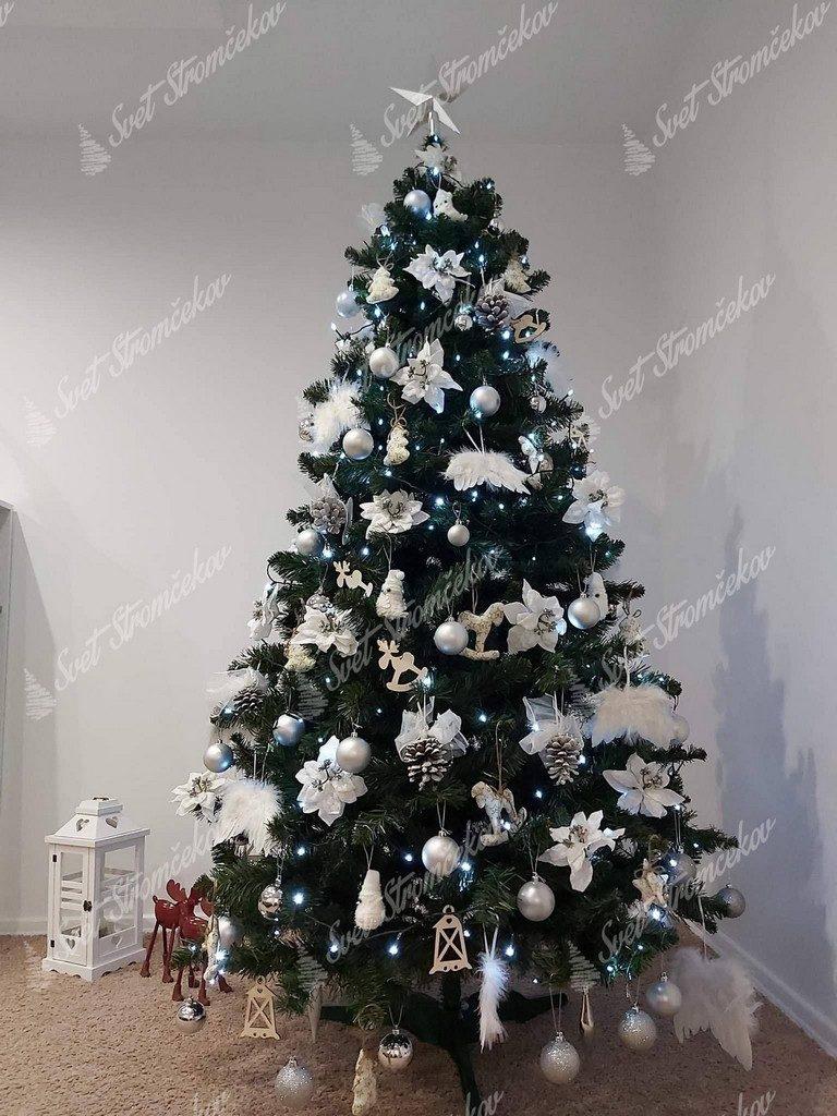 Zelený vianočný stromček ozdobený bielými kvetmi , šiškami a anjelskými krídlami .
