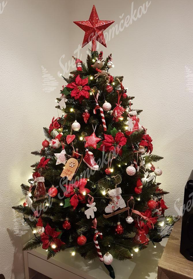 Zelený vianočný stromček smrek ozdobený červenými kvetmi a hviezdičkami.