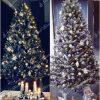 Ozdobený zasnežený biely vianočný stromček bielými a modrými vianočnými ozdobami