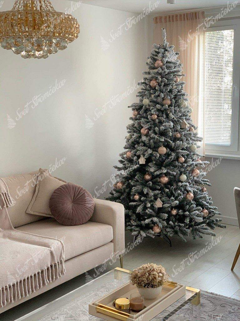 Zasnežený vianočný stromček ozdobený zlatými a pudrovými vianočnými ozdobami.