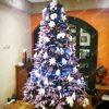 Fialový vianočný stromček ozdobený bielými kvetmi a vianočnými ozdobami