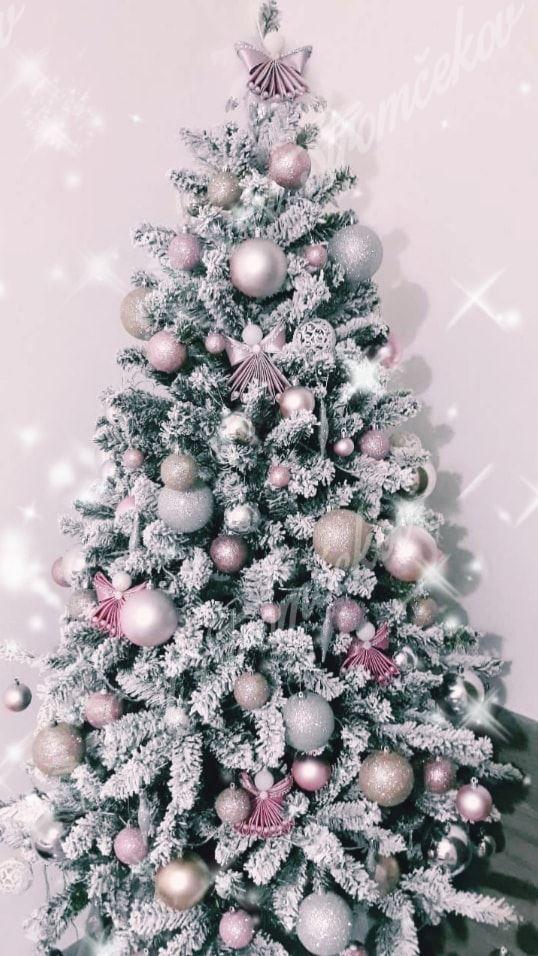 Biely vianočný stromček ozdobený striebornými a ružovými gulami.