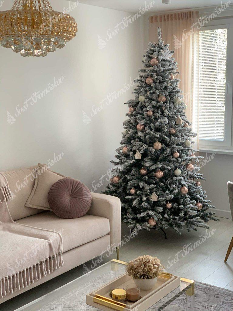 Biely vianočný stromček decentne ozdobený púdrovými ozdobami na stromček v modernej obývacej izbe .