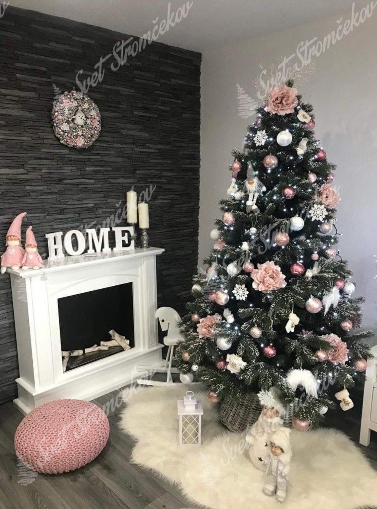 Zelený vianočný stromček so zasneženými končekmi vetvičiek pri krbe. Stromček ozdobený ružovkastými kvetmi a bielymi anjelskými krídlami .