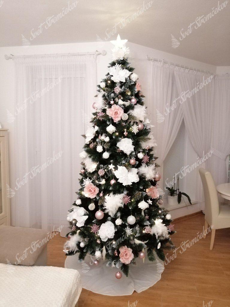 Zelený vianočný stromček ozdobený bielymi vianočnými kvetmi a bledo ružovými ružami .