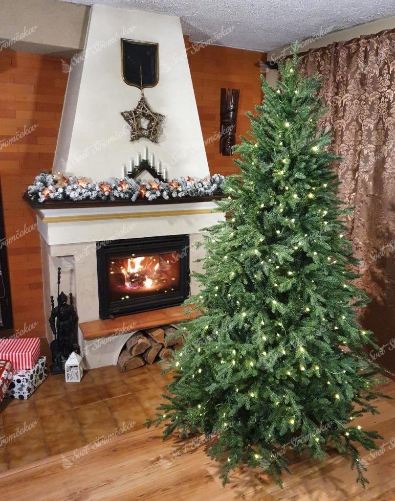 Svietiaci vianočný stromček 3D Smrek Horský pri rozhorenom krbe. Celá miestnosť je vianočne ozdobená.