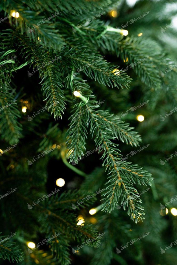 Vetvička vianočného stromčeka s realistickým 3D ihličím. Vetvička je omotaná LED vianočným osvetlením.