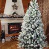 Biely vianočný stromček vo vianočne vyzdobenej miestnosti s krbom.