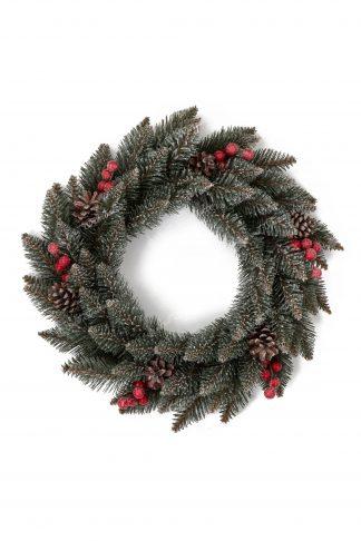 Pohľad zhora na vianočný veniec tyrkysovej zelenej farby doplnený šiškami s borovice a červenými lesnými plodmi.
