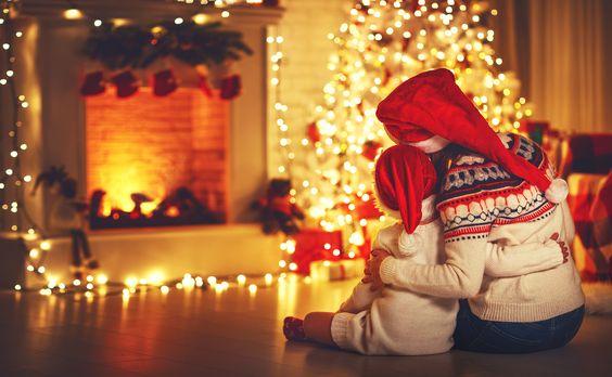 Deti dívajúce sa na rozsvietený vianočný stromček.
